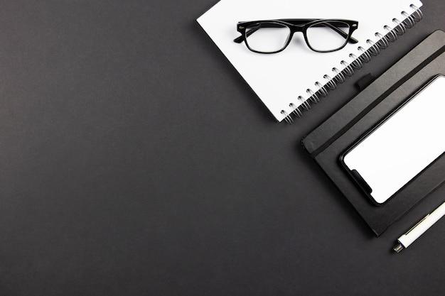 Плоский современный офисный стол с макетом экрана смартфона, спиральным бумажным блокнотом и очками для чтения на темной поверхности