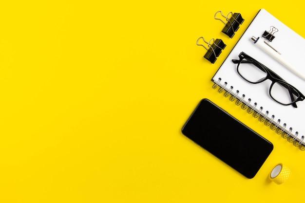 Плоский современный офисный стол с макетом экрана смартфона, спиральным бумажным блокнотом и очками для чтения на желтой поверхности