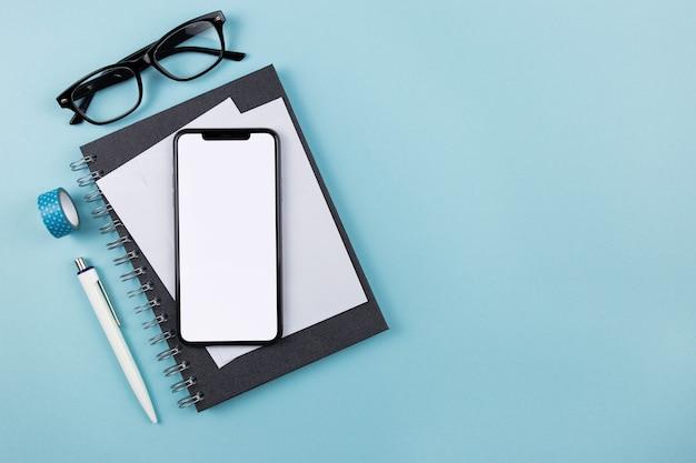 Плоский современный офисный стол с макетом экрана смартфона, спиральным бумажным блокнотом, белыми конвертами и очками для чтения на синей поверхности