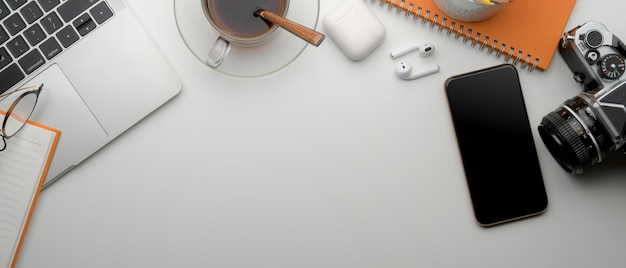 Modern office desk with copy space, smartphone, laptop, coffee cup and supplies