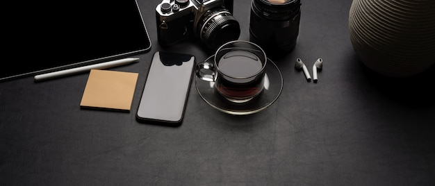 Modern office desk with digital supplies, camera, coffee cup, notepad and decoration on black leather table