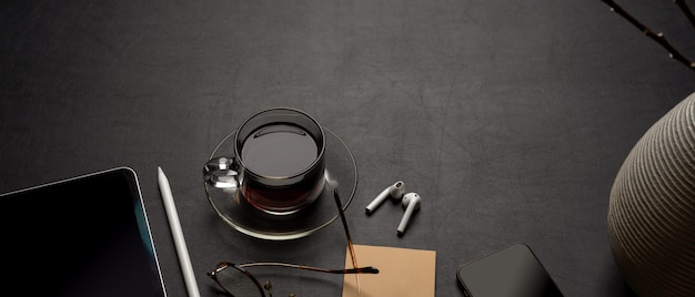 Modern office desk with digital supplies, coffee cup, notepad, glasses and decoration on black leather table