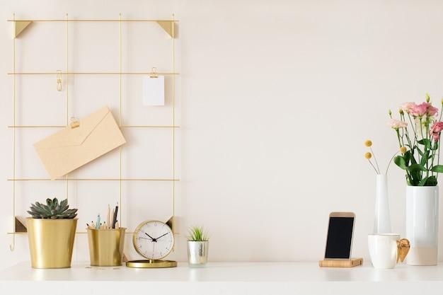ゴールドのアクセサリーが付いたモダンなオフィスデスク。空のスペース、モックアップ。ミニマルなスタイル。