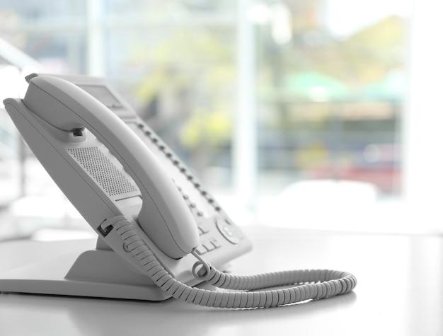 Современный офисный ip-телефон на светлом размытом фоне