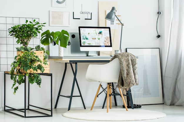Современная офисная комната с дизайнерским стулом на белом ковре и серой лампой на столе
