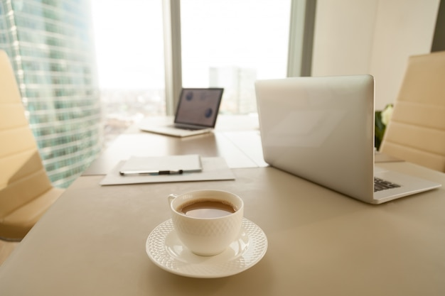 Modern office workplace, coffee cup, laptops on conference negot