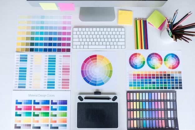 Современное офисное рабочее место с планшетом, графическим дизайнером и образцами образцов цвета на рабочем месте, рабочее пространство с видом сверху.
