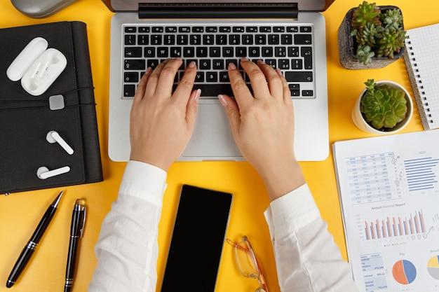 現代のオフィスの黄色い机とビジネスウーマンの手でノートパソコンの上面図を入力