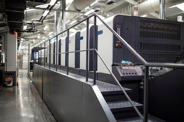Modern offset printing press machine in print house.