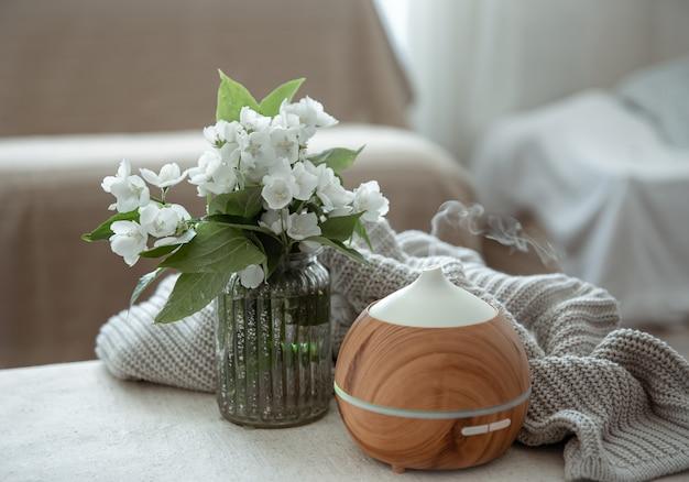 Современный масляный ароматизатор в гостиной на столе с вязанным элементом и цветами.