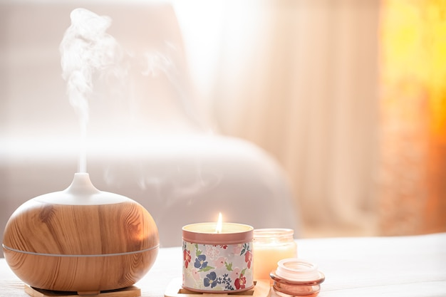 Modern oil aroma diffuser in the living room on the table with burning candles.