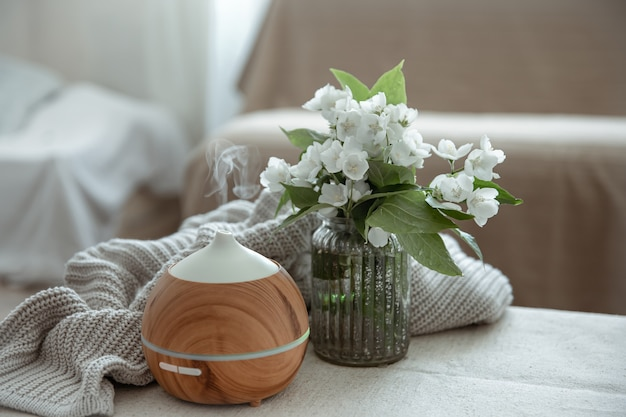 Modern oil aroma diffuser in the living room on the table with knitted element and flowers.