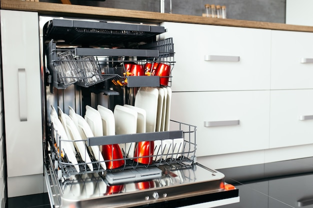 흰색 주방에 깨끗한 접시가 있는 현대적인 개방형 식기 세척기.