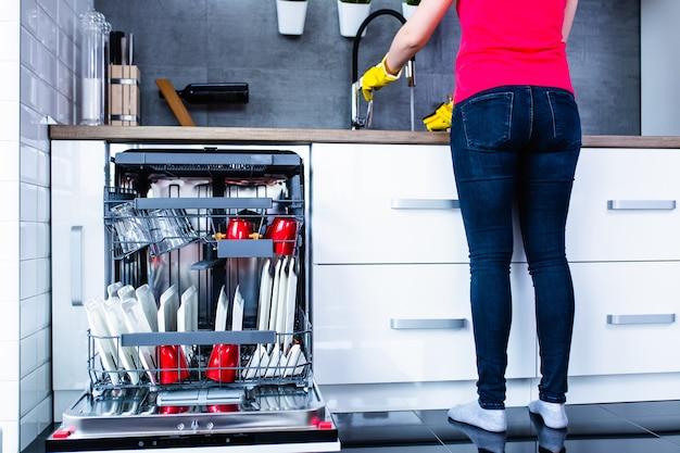 Современная открытая посудомоечная машина с чистой посудой на белой кухне.