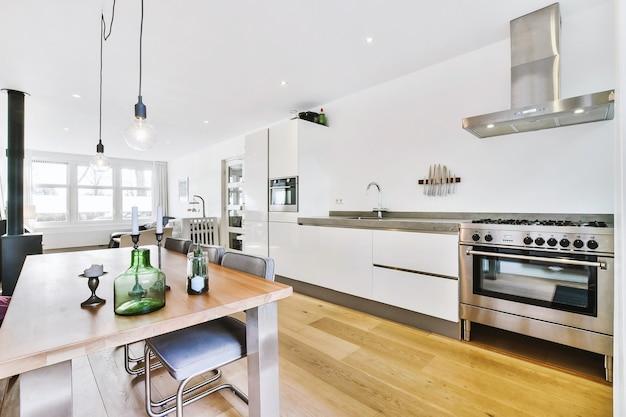Современная кухня открытого плана с белыми шкафами и обеденным столом в комнате-студии с диваном и камином