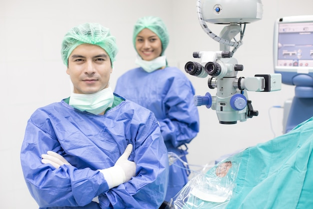 In a modern operating room doctor and team looking to camera with smile.