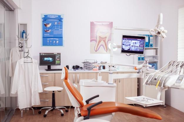 滅菌器具を備えたモダンなオレンジ色の歯科医用キャビネット。誰も入っていない口腔病学用キャビネットと、口腔治療用のオレンジ色の器具。