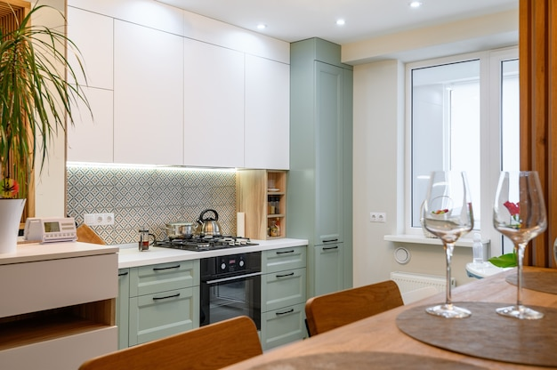 Modern orange white and teal kitchen interior with dining zone
