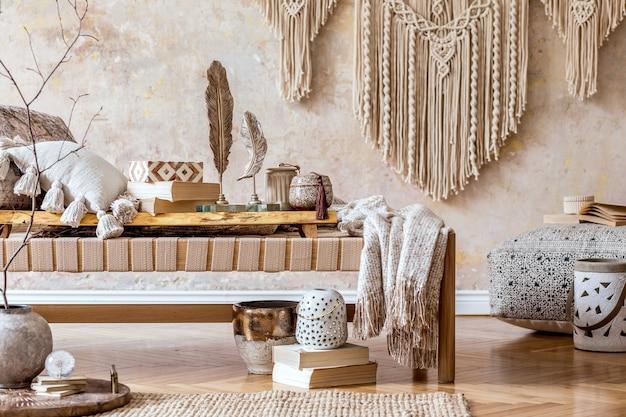 Современная восточная гостиная с дизайнерским бежевым шезлонгом, красивым макраме, подушками, деревянным подносом, книгой, декором и элегантными личными аксессуарами в домашнем декоре.