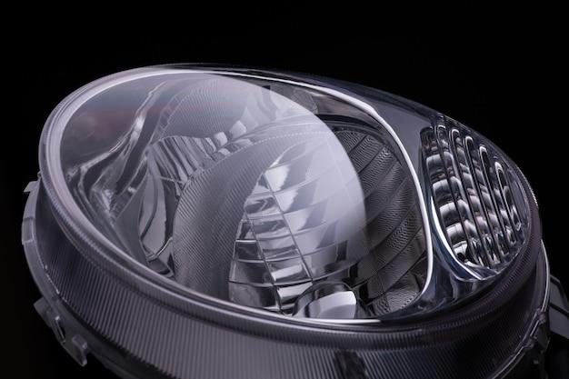 검정색 배경에 자동차의 현대적인 타원형 헤드라이트. 외딴