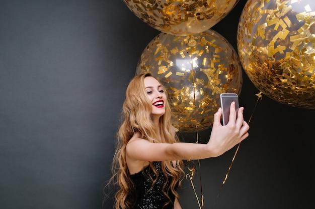 Tempo di festa moderno di giovane donna splendida in abito di lusso nero, con lunghi capelli biondi ricci che fanno selfie con grandi palloncini pieni di orpelli dorati. celebrare, sorridere.