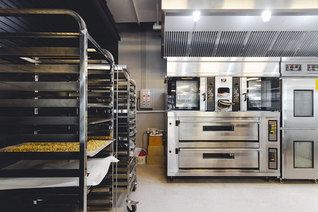 Modern pastry kitchen decorated in black, white and steel with baking machine,