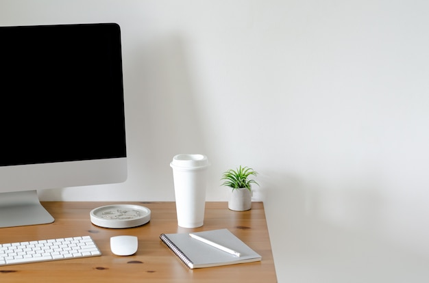Modern personal computer screen on wooden table with a cup of coffee and tillandsia air plant