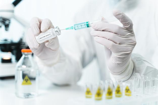현대약국. 새로운 백신 샘플을 채취하면서 직장에 앉아 있는 전문 과학자