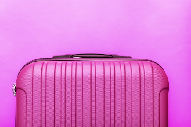 Modern pink suitcase on pink background close up with copy space for text. minimal style travel concept.