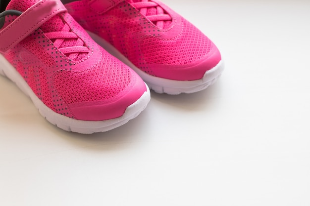 現代の小指スポーツシューズ。カラフルな背景のスポーツシューズのペア。柔らかい緑の背景に新しいスニーカー、コピースペース。ランニングシューズ。ピンクのスニーカー。女の子のためのピンクのトレーニングシューズのペア。女性の女性