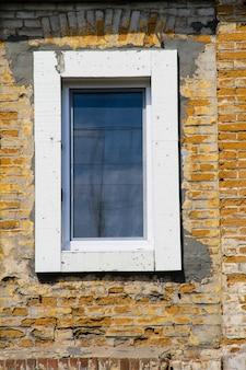 古いレンガの壁にモダンなプラスチックの窓
