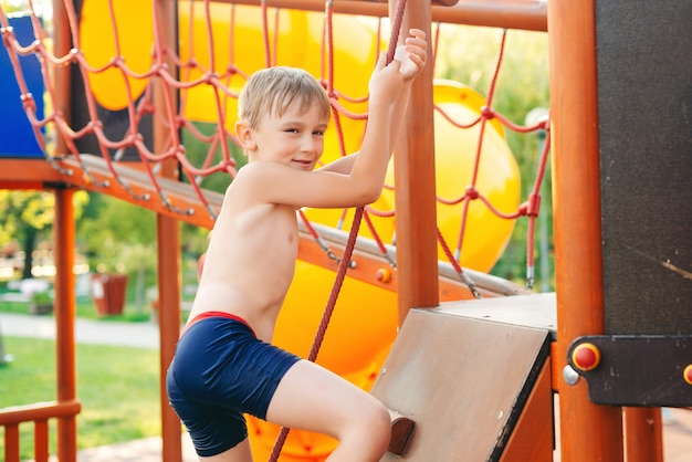 바다 해변에서 현대 놀이터입니다. 놀이터에서 등반하는 아이.