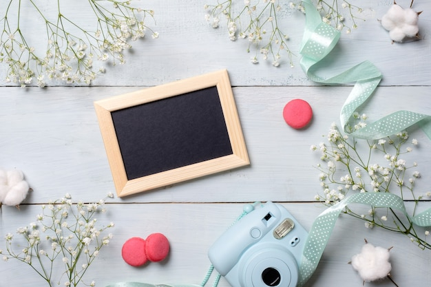 Modern polaroid camera, macaroon cookies, photo frame, flowers on rustic blue wooden background.