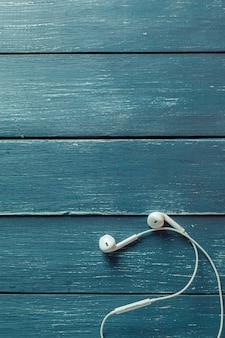 Modern portable audio earphones on wood board background
