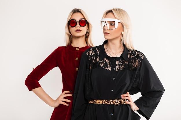 Современный портрет двух девочек-подростков в цветных очках со светлыми волосами в красно-черных платьях, стоящих возле старинной серой стены