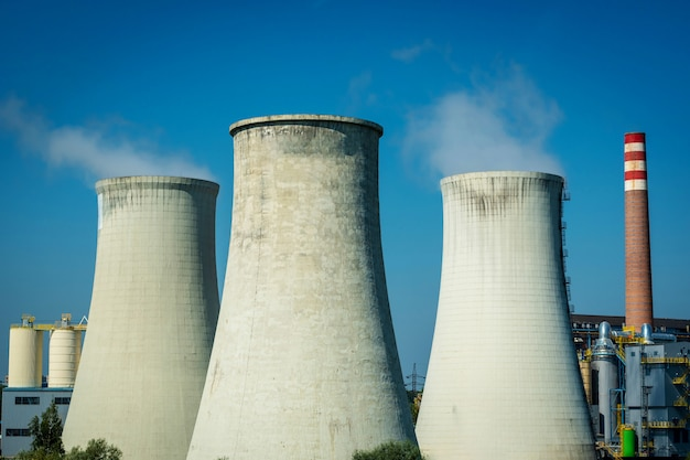 Modern power station cooling towers against a blue sky.