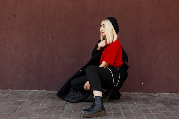 Modern pretty beautiful woman  blonde with sexy red lips in a black beret in a long trendy autumn coat in a red t-shirt in boots posing sitting near to a vintage wall