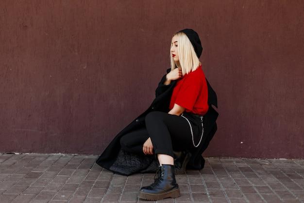 ヴィンテージの壁の近くに座ってポーズをとっているブーツの赤いtシャツの長い流行の秋のコートの黒いベレー帽のセクシーな赤い唇を持つ現代のかなり美しい女性のブロンド