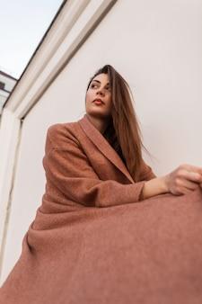 현대 꽤 우아한 세련 된 여성 패션 모델 도시에서 빈티지 흰색 벽 근처 유행 베이지 색 긴 코트에 포즈. 야외에서 아름 다운 섹시 한 여자입니다. 여성을위한 세련된 계절 의상.