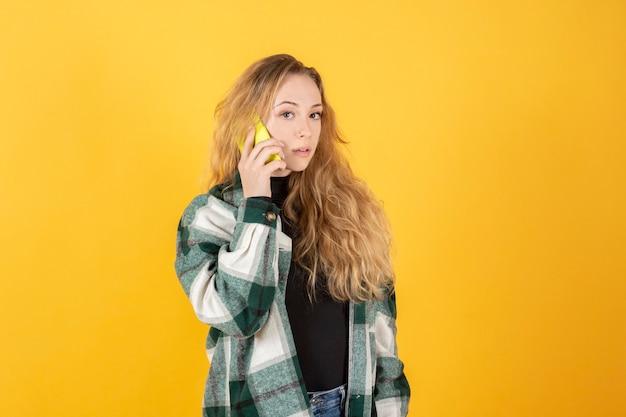 Современная красивая женщина разговаривает со своим смартфоном на желтом фоне