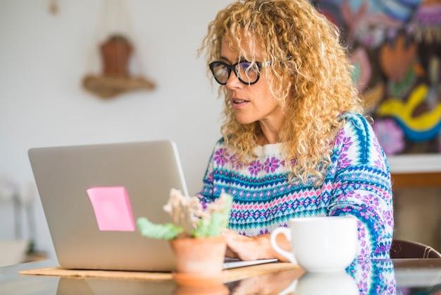 현대 예쁜 여자가 일하고 대체 사무실과 무료 라이프 스타일에서 집에서 노트북 컴퓨터 기술과 인터넷 연결을 즐기십시오.