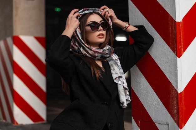スタイリッシュな服を着た現代のかなり若い女性は、屋外の頭にヴィンテージのシルクスカーフを置きます。トレンディな黒いコートを着た濃いサングラスの美しい少女が通りの赤白の縞模様の柱の近くでポーズをとるエレガンス