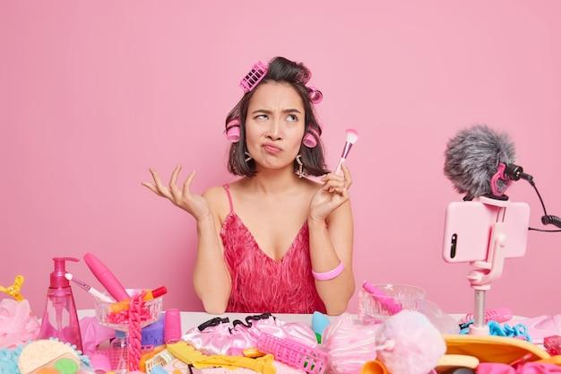 Современная профессия. озадаченная недовольная азиатка держит косметические кисти, записывает видео дома, дает советы женщинам, делает онлайн-перевод, дома делает прическу