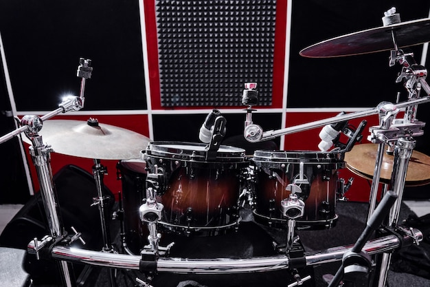 Modern professional drum kit on a rehearsal base close-up, red and black recording studio