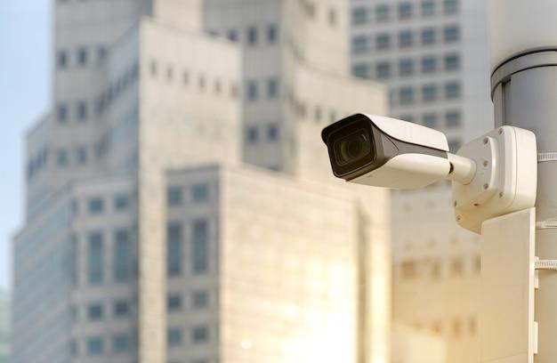 Современная общественная камера видеонаблюдения на электрическом столбе на размытом фоне здания с копией пространства