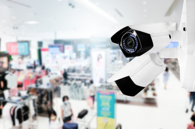 Modern public cctv camera with blur interior shopping mall background and copy space.
