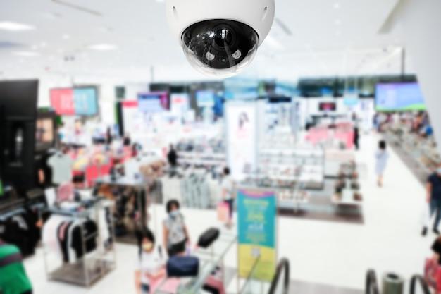 Современная общественная камера видеонаблюдения с размытым интерьером торгового центра