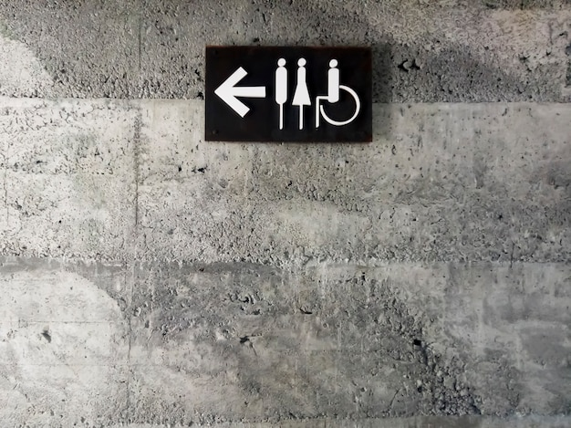 Modern public toilet sign on the cement wall. toilet icon sign on concrete wall . mens and womens disabled restroom signage with arrow made from steel plate on grey concrete wall.