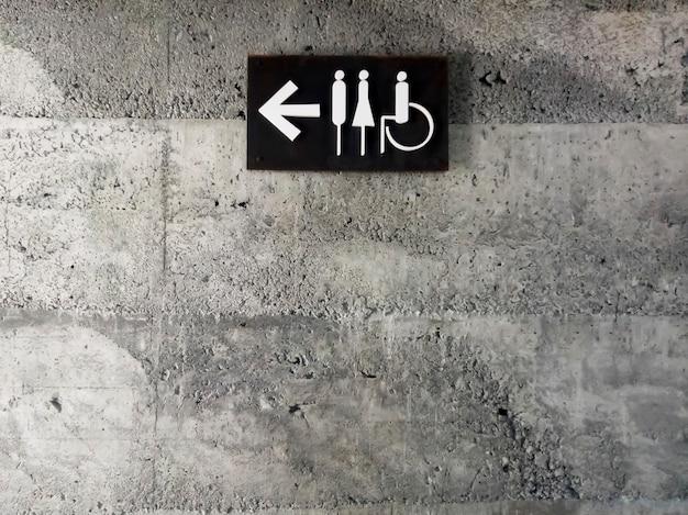 시멘트 벽에 현대적인 공중 화장실 표지판. 콘크리트 벽에 화장실 아이콘 기호입니다. 회색 콘크리트 벽에 철판으로 만든 화살표가 있는 남녀 장애인 화장실 표지판.