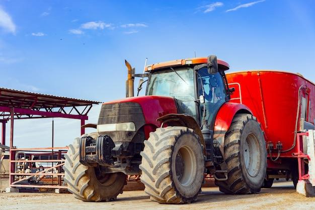 Современный красный сельскохозяйственный трактор вождения на ферме